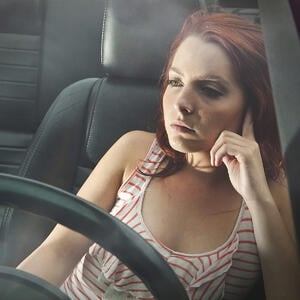 Woman daydreaming in car