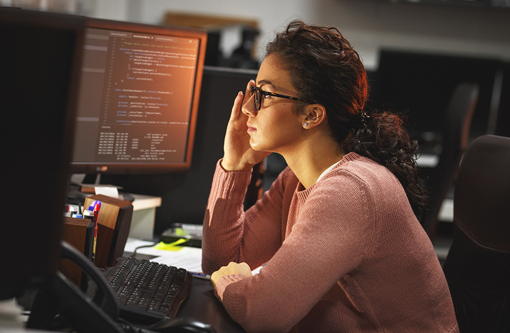 Female data analyst reviewing code at her desk.
