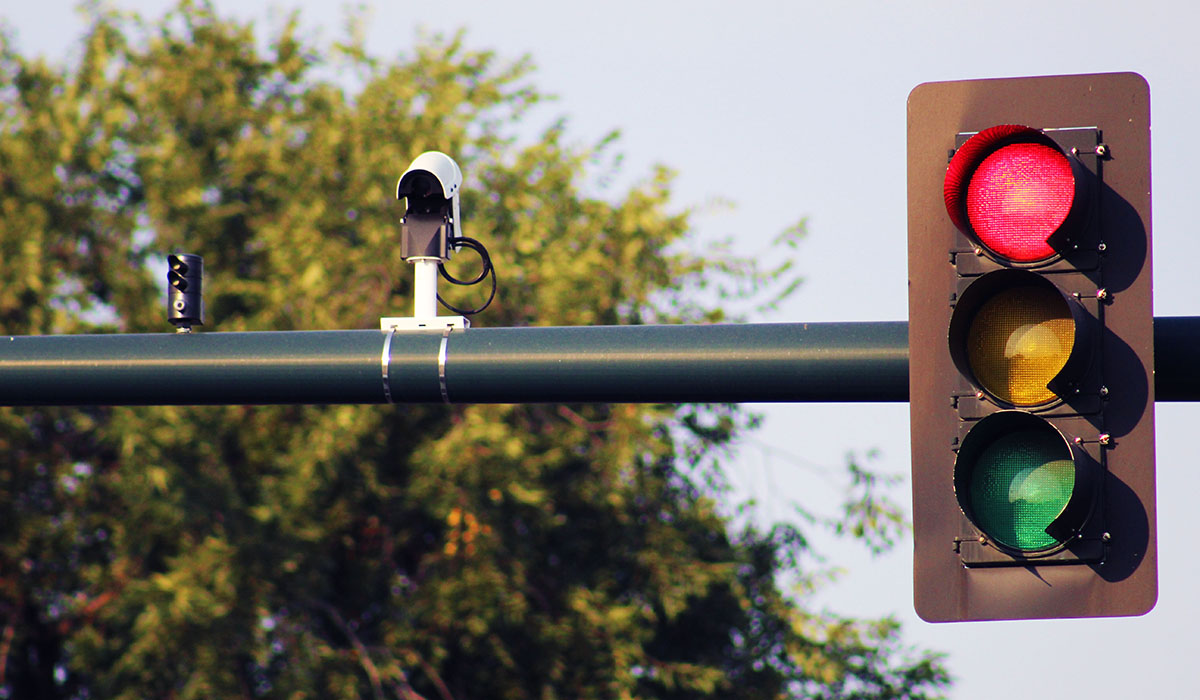 Camera mounted on a traffic signal pole next to a traffic signal showing a red light.