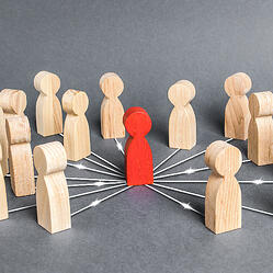 Chess pieces surrounding a red chess piece to show leadership with directional arrows pinting to each chess piece from the red chess piece